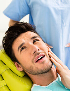 Young man in dental chair holding cheek