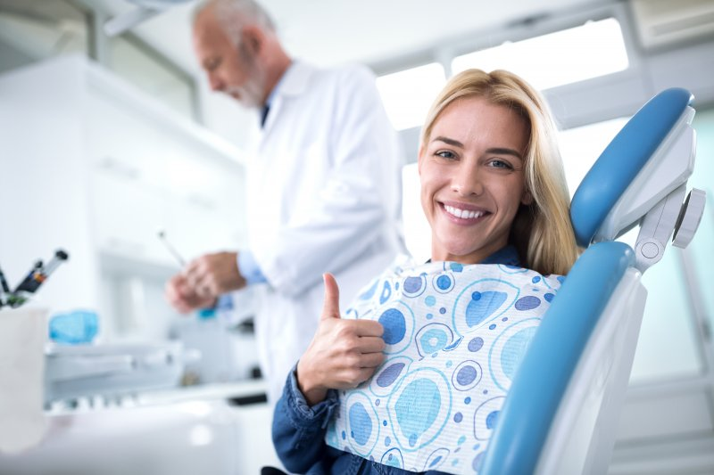 Woman smiling and giving thumbs up in treatment chair